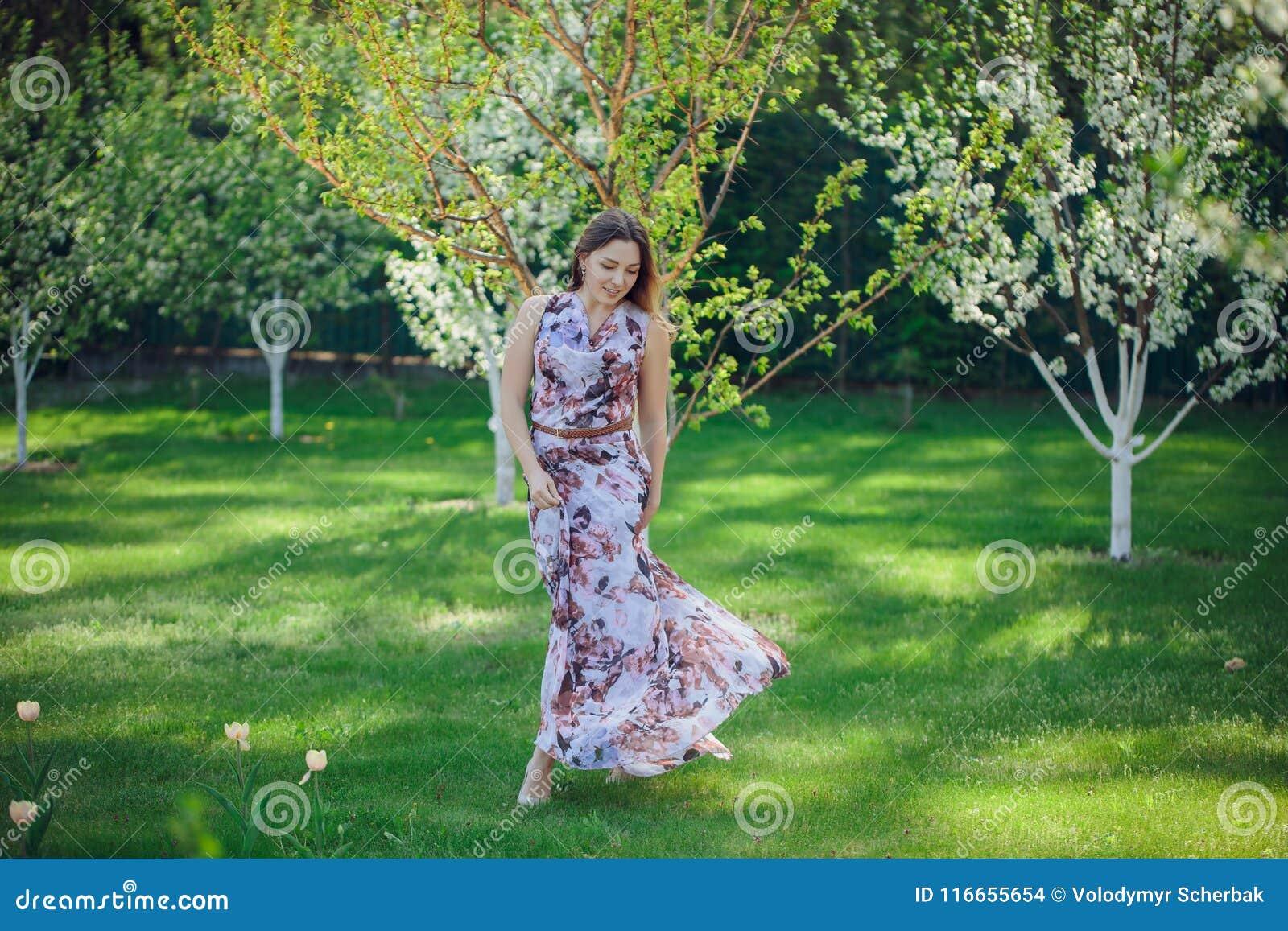Belle femme heureuse de portrait appréciant l odeur dans un jardin de floraison de ressort fleurissant Fille de sourire intellige