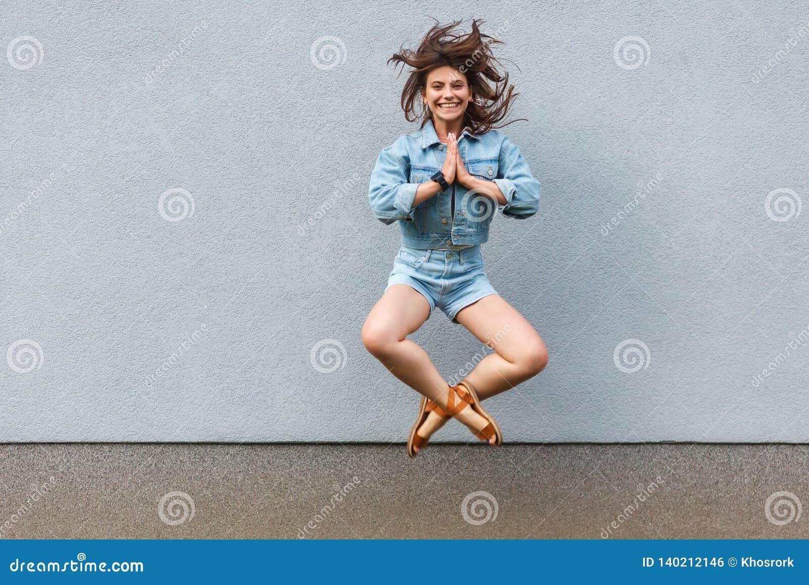 Belle femme heureuse libre dans le style occasionnel de denim de jeans dans l été sautant au mur bleu-clair avec des mains de pau