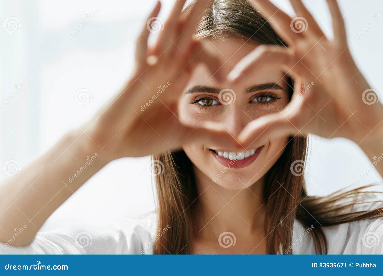 Belle femme heureuse montrant le signe d amour près des yeux
