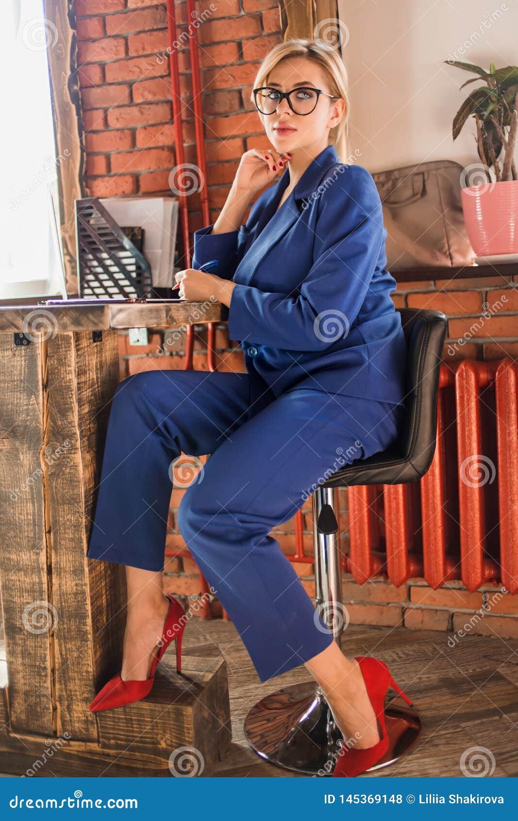 Belle femme intelligente d affaires s asseyant à la table au poste de travail avec l ordinateur portable