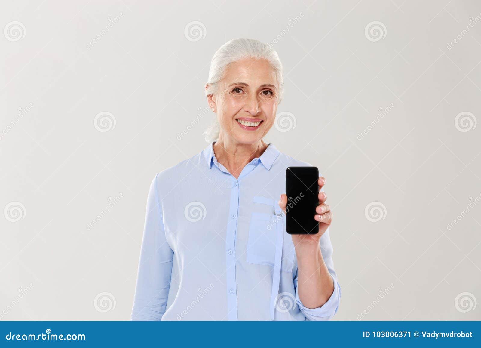 Belle femme mûre heureuse montrant le smartphone avec l écran noir vide d isolement