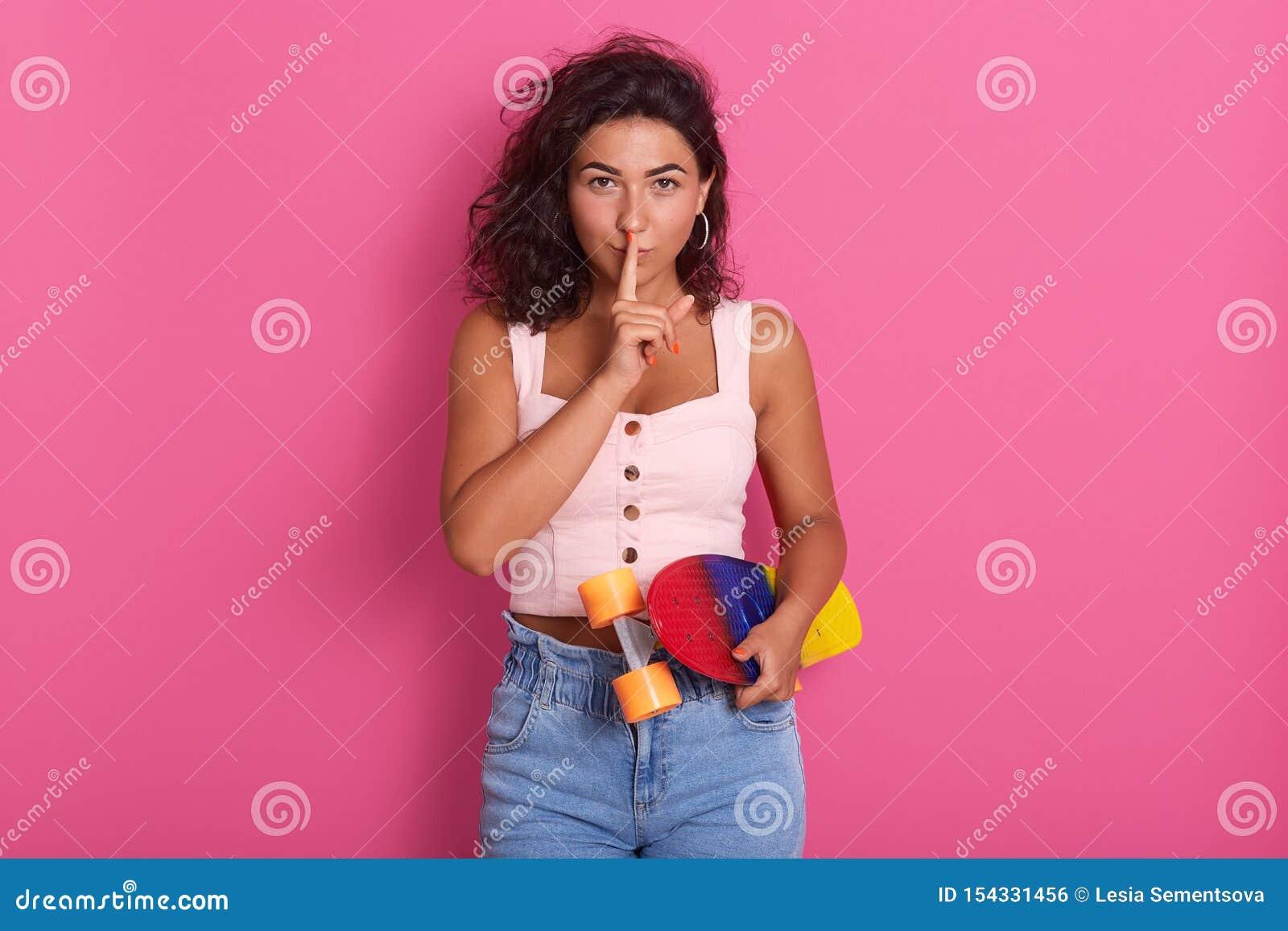 Belle femme magnifique mettant son index aux lèvres, maintenant silencieux, regardant directement la caméra, jugeant coloré