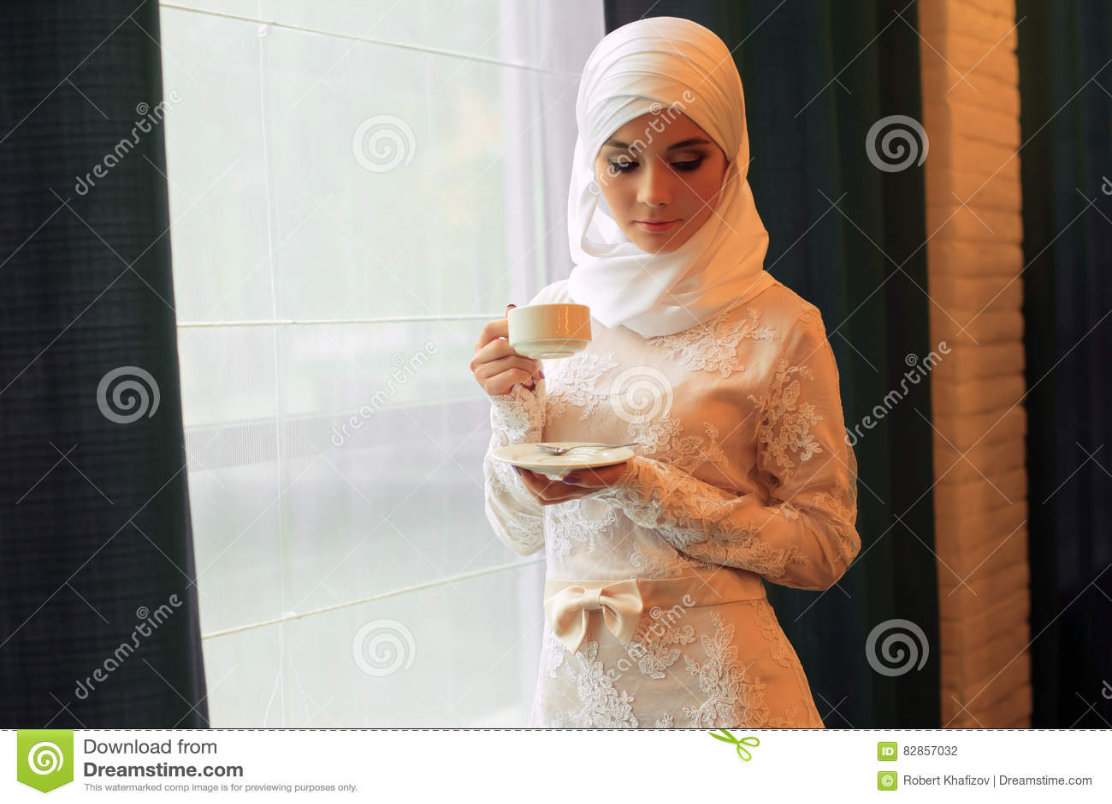 Belle femme musulmane dans une robe de mariage blanche avec une tasse de  thé dans des
