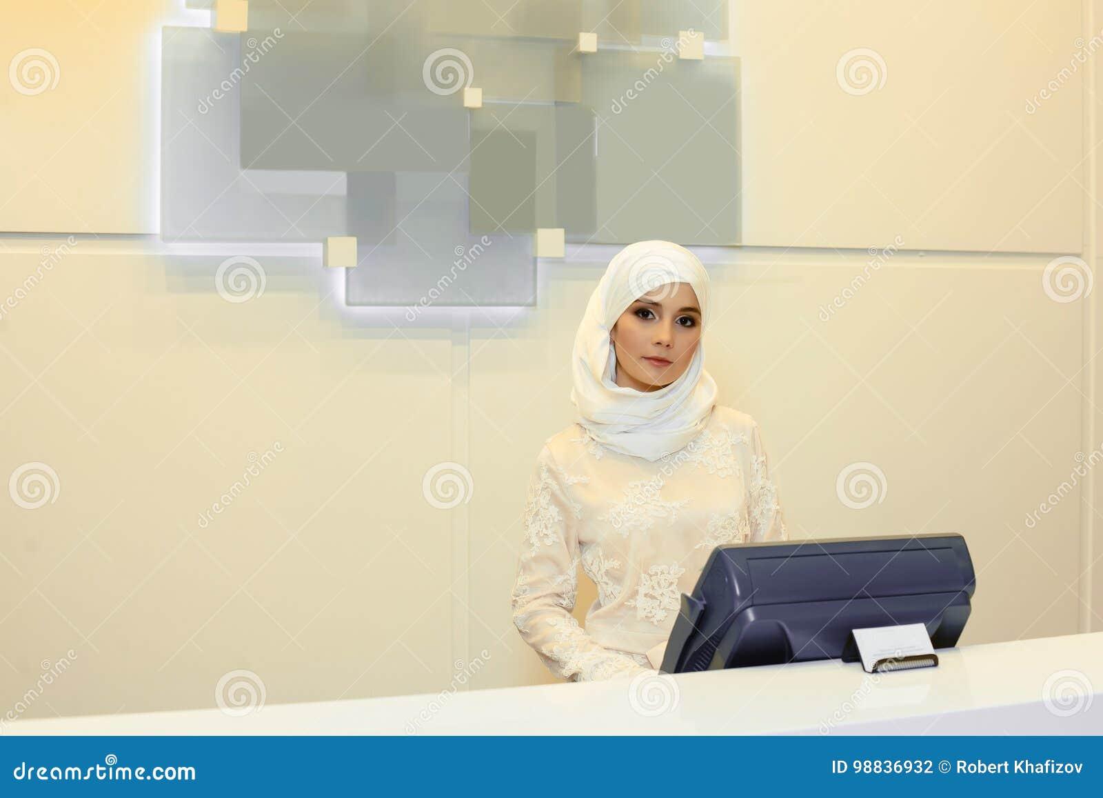 Belle femme musulmane se tenant derrière la réception dans l hôtel