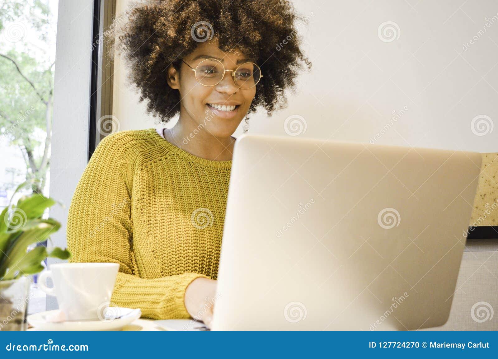 Belle femme noire d étudiant souriant au café potable d ordinateur portable