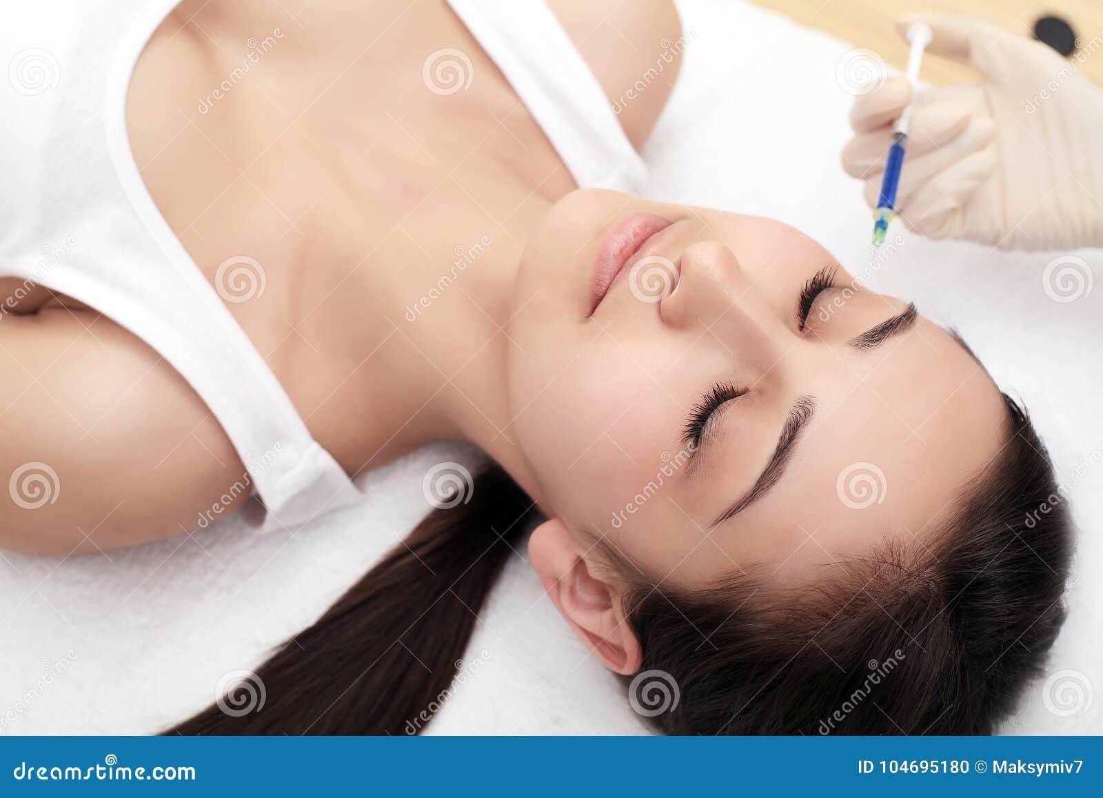 Belle femme obtenant l injection de levage de botox dans le front Injection en gros plan d acide hyaluronique de femme injections