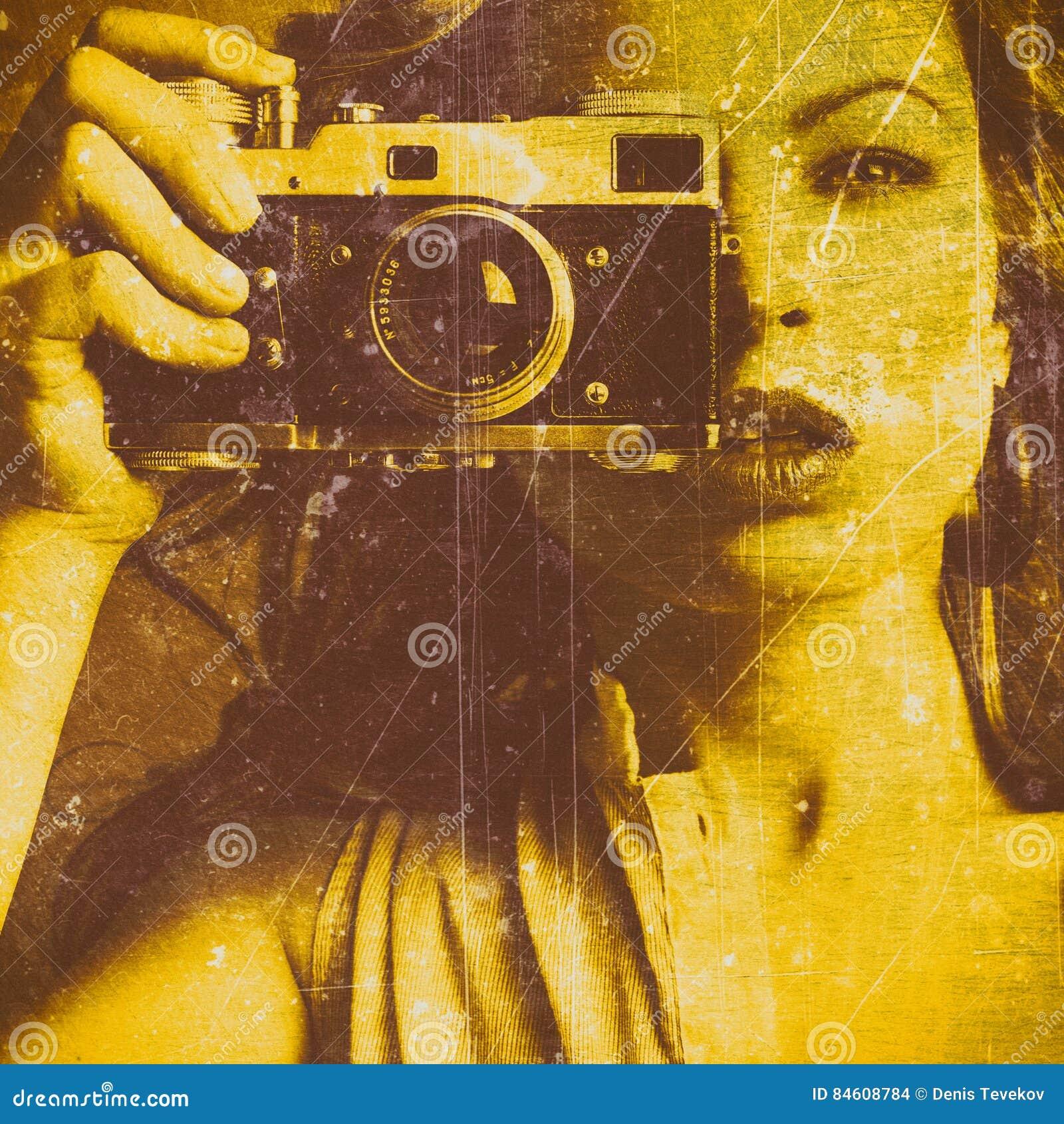 Belle femme prenant des photos avec le rétro appareil-photo de film