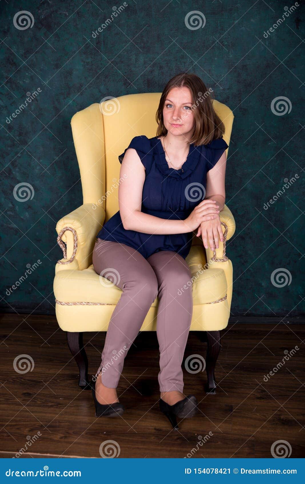 Belle femme s asseyant sur le grand fauteuil dans le studio