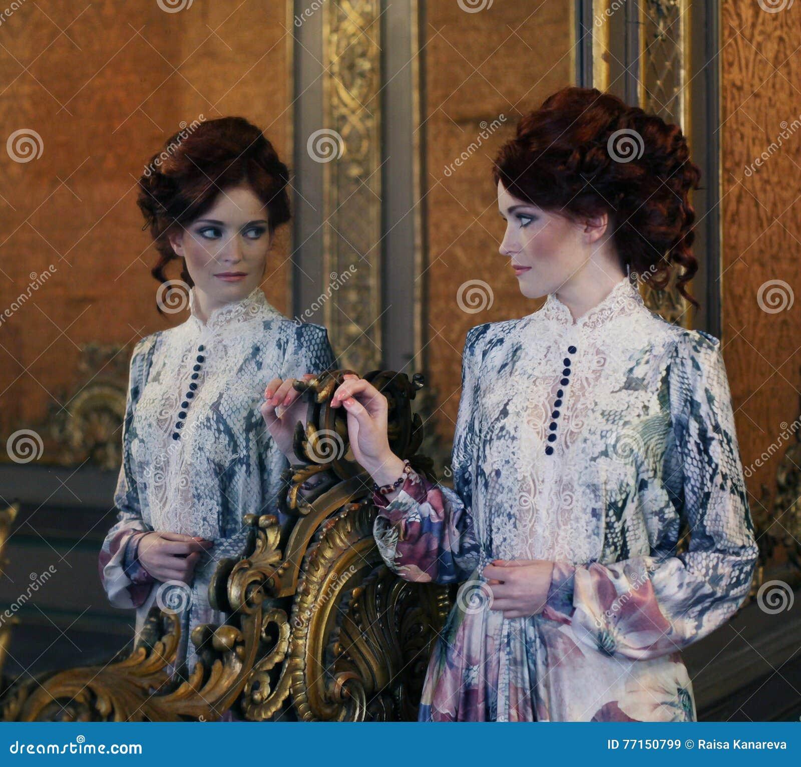 Belle femme se tenant dans la salle de palais avec le miroir