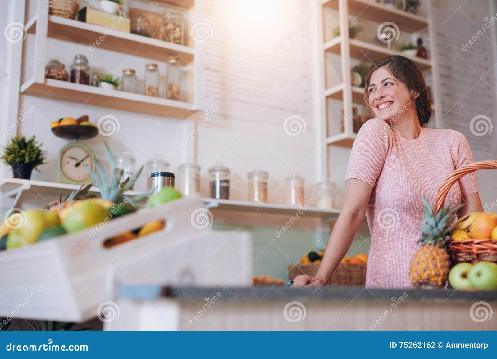 Belle femme se tenant derrière le compteur de son bar à jus