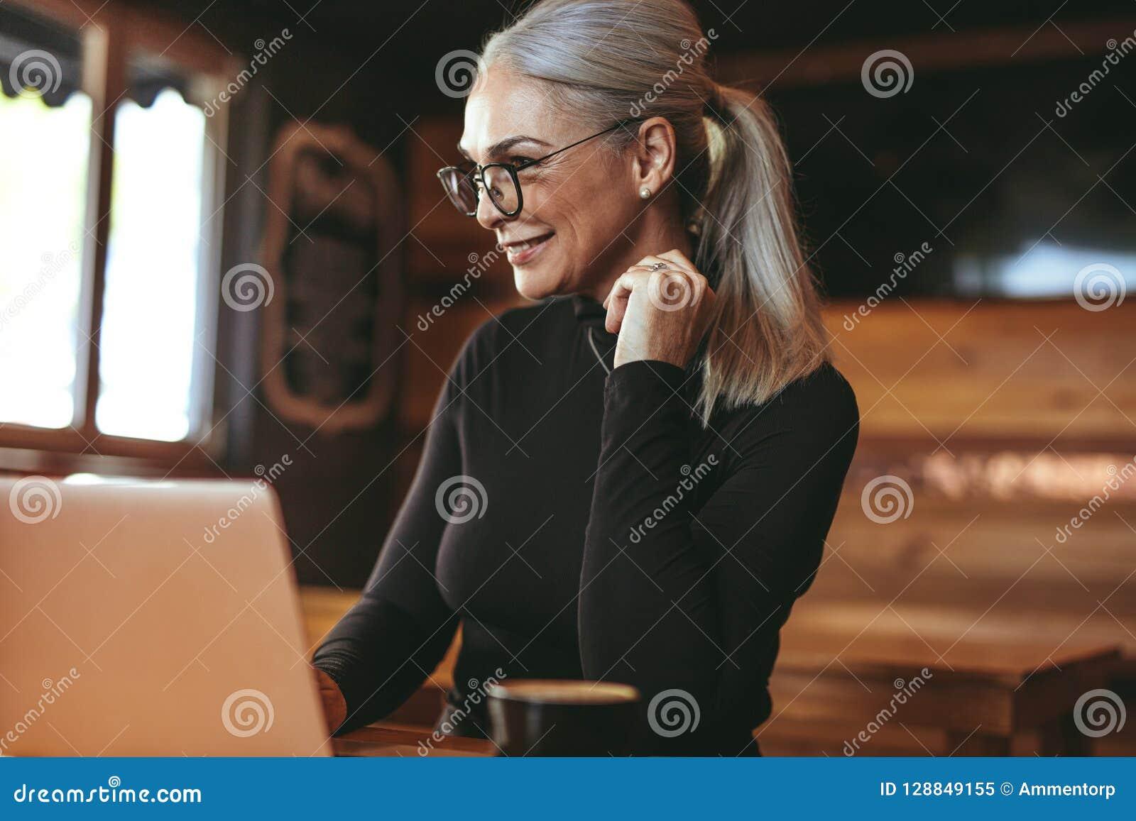 Belle femme supérieure au café utilisant l ordinateur portable