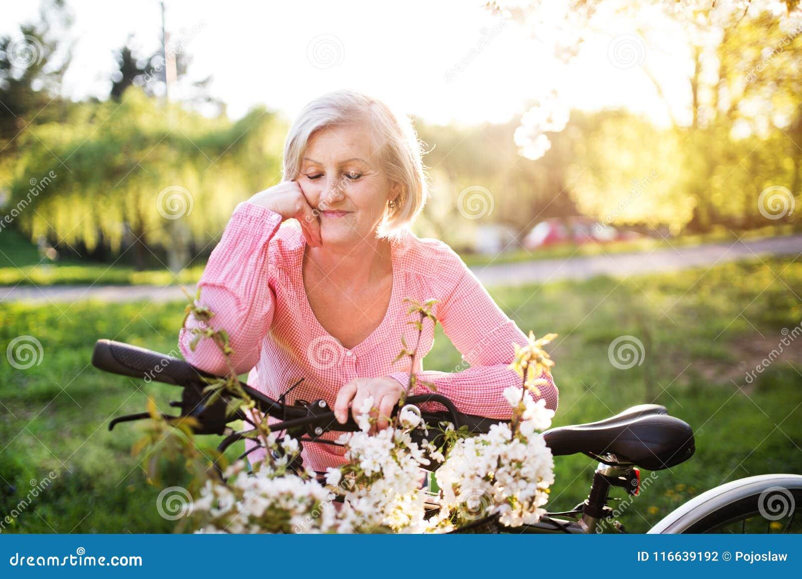 Belle femme supérieure avec la nature d extérieur de bicyclette au printemps