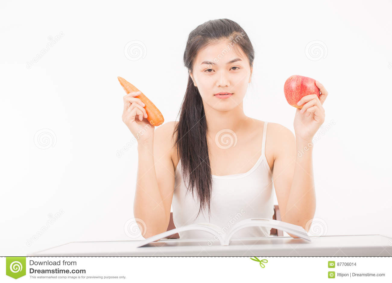 Belle femme tenant la carotte et la pomme