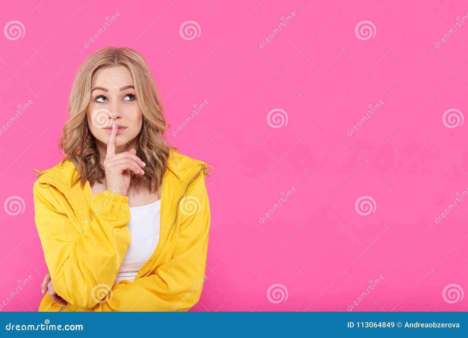 Belle fille à la mode dans des vêtements colorés profondément dans les pensées, recherchant avec le doigt sur des lèvres Portrait