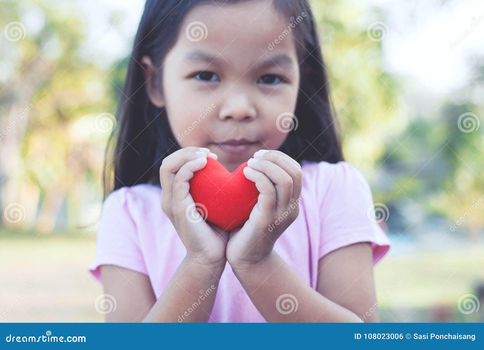 Belle fille asiatique de petit enfant avec le coeur rouge