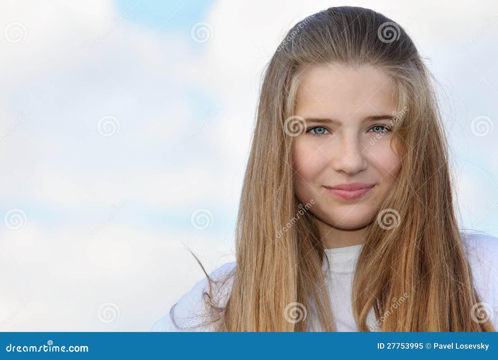 Belle fille avec de longs sourires de cheveu