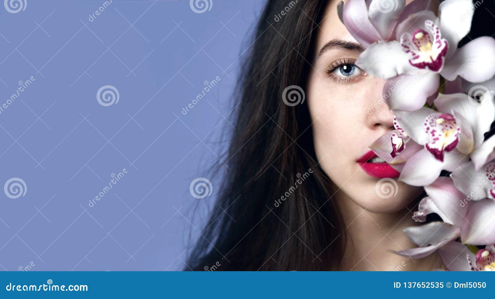 Belle fille avec des fleurs d orchidée Visage de femme de modèle de beauté sur le fond pourpre