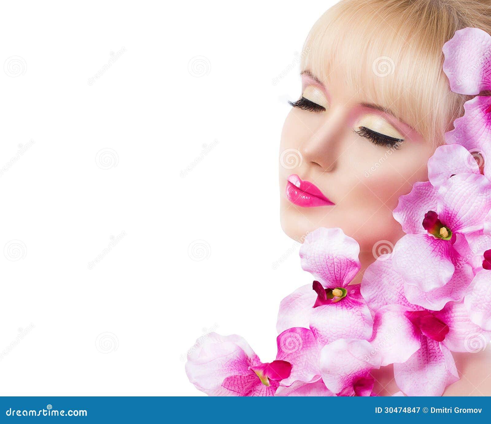 Belle fille avec des fleurs et maquillage parfait sur le backgrou blanc