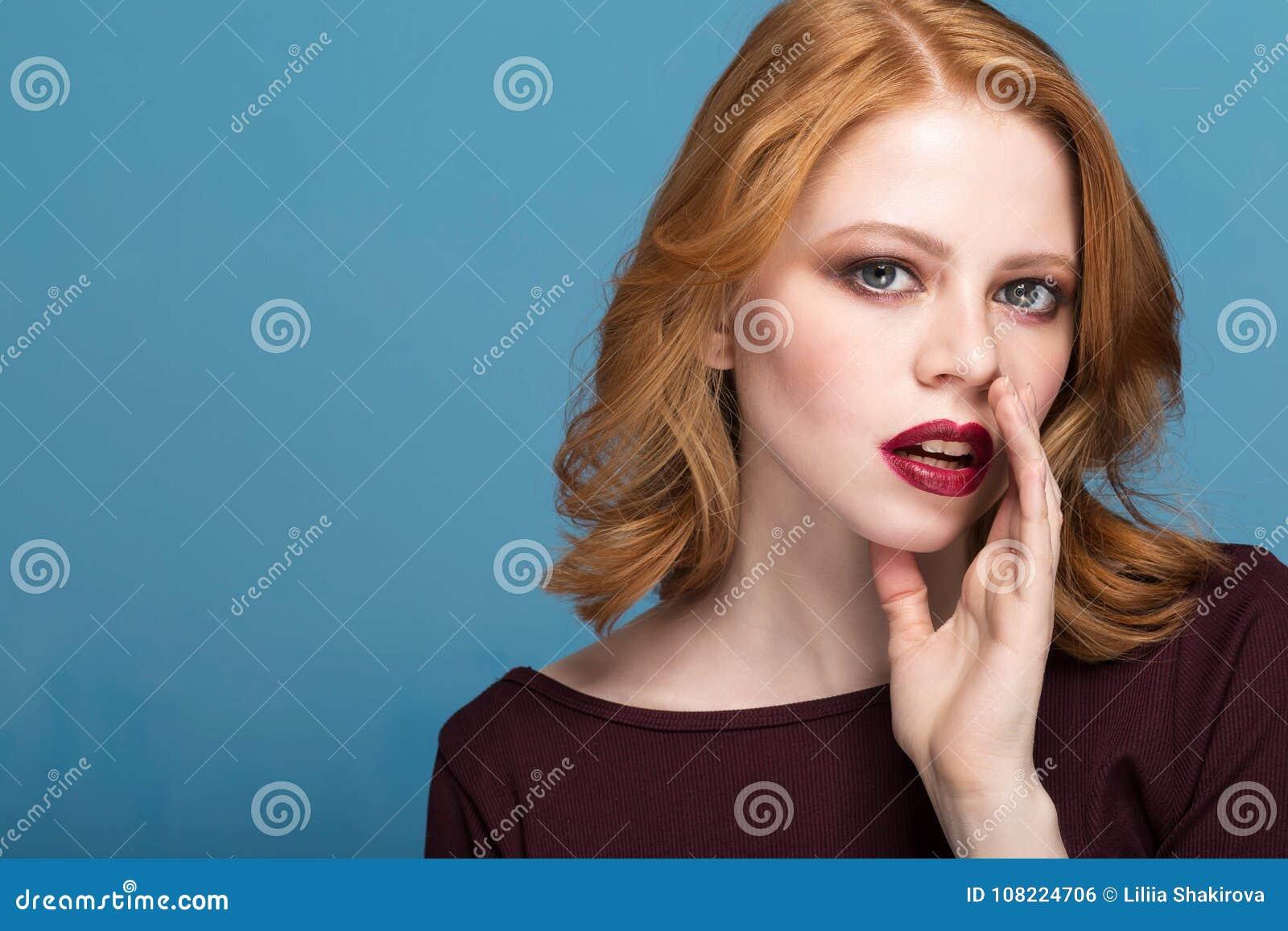Belle fille avec le maquillage lumineux et les cheveux bouclés indiquant un secret Jeunes de portrait