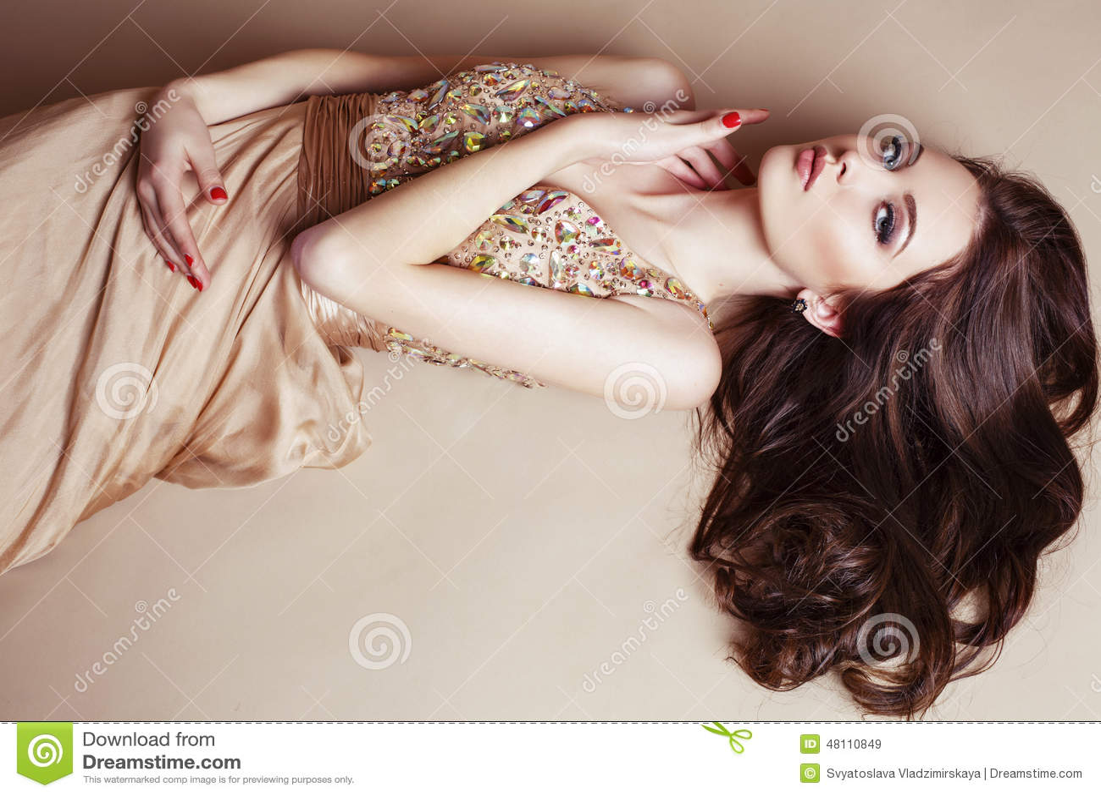 Belle fille avec les cheveux foncés luxueux dans la robe de paillette posant au studio