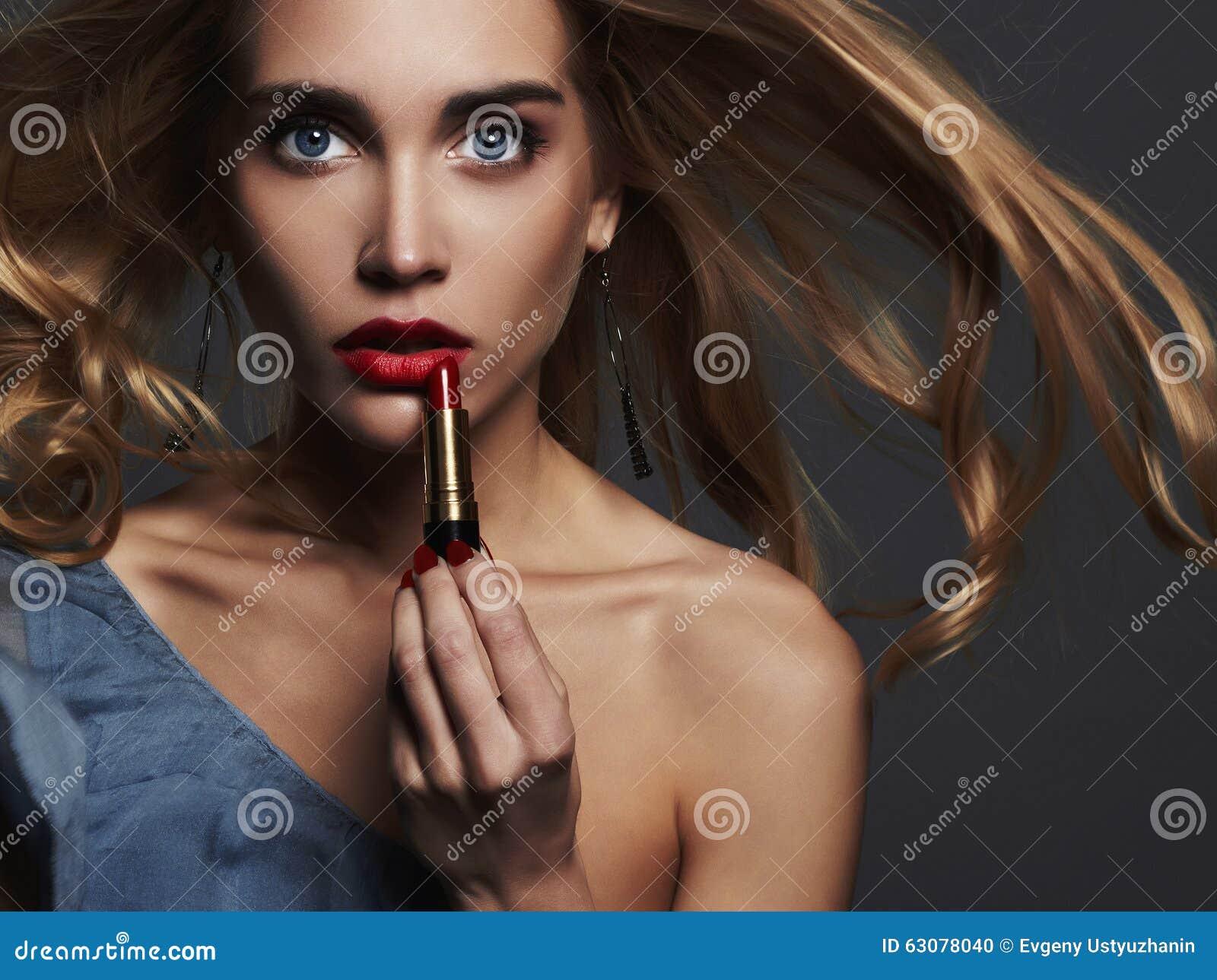 Download Belle Fille Avec Les Languettes Rouges Jeune Femme Mettant Lipstic Rouge Photo stock - Image du âge, tête: 63078040