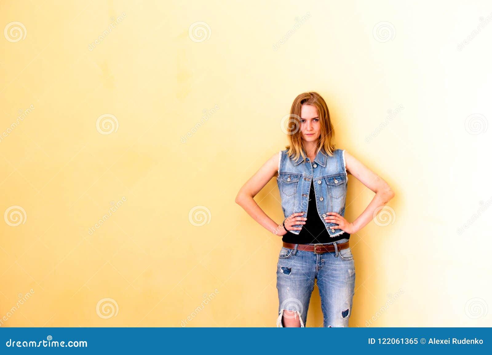 Belle fille avec ses cheveux se tenant sur le fond jaune d isolement Elle avec tout son aspect dépeint l émotion de la passion