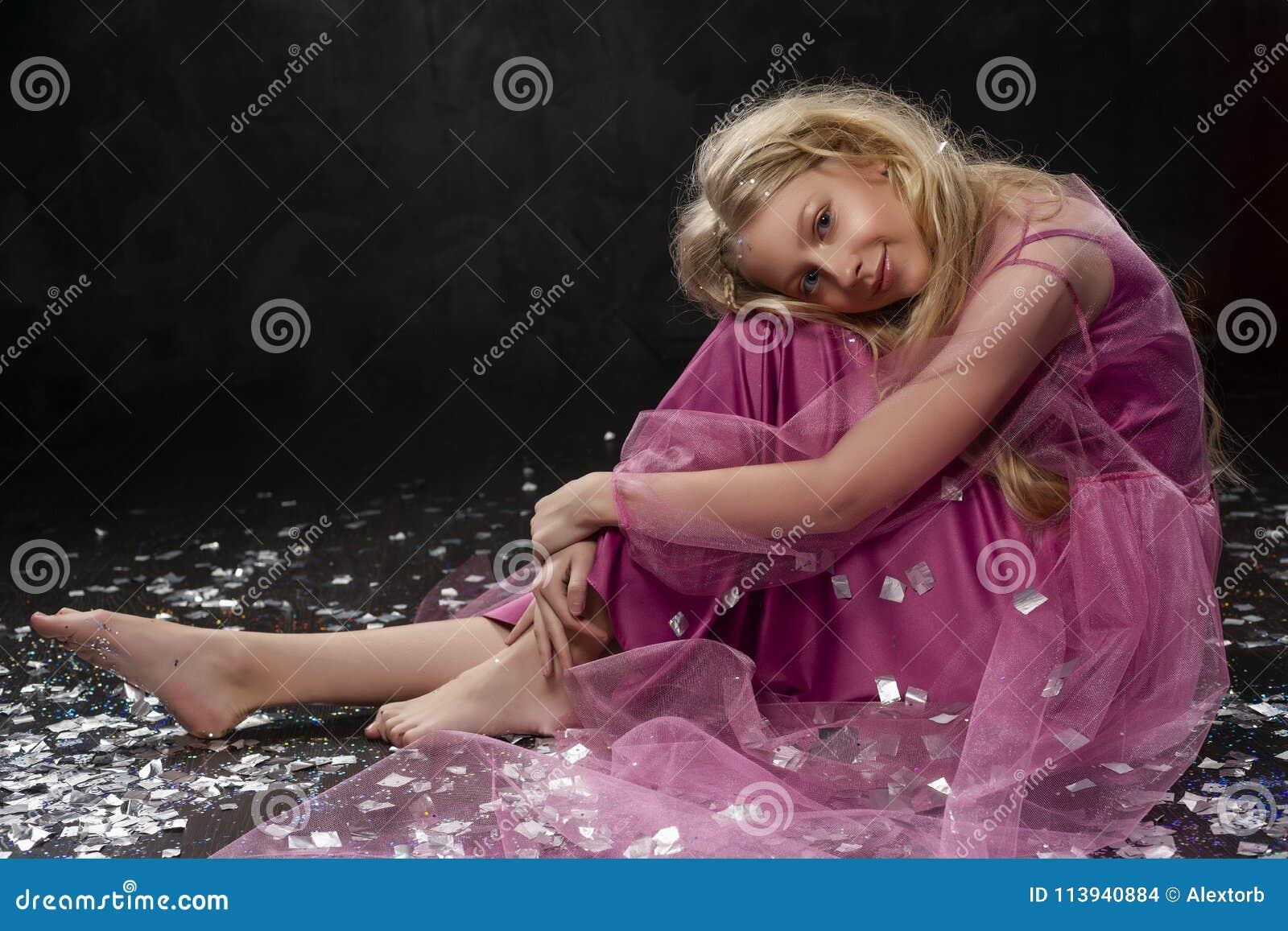 Belle fille blonde bouclée d enfant d adolescent portant un Dr. rose d air