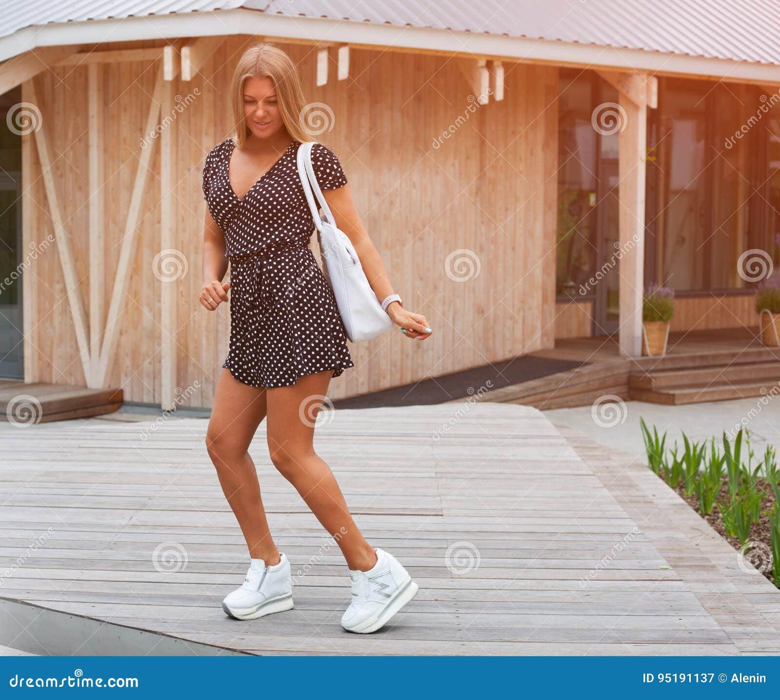 belle fille blonde dans la robe de short d 39 t et des espadrilles la mode blanches dansant. Black Bedroom Furniture Sets. Home Design Ideas
