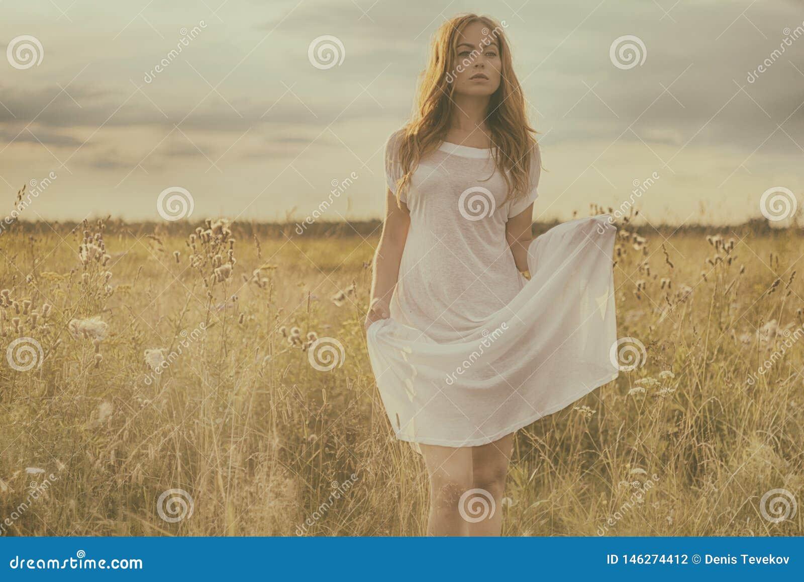 Belle fille blonde sur le champ vert avec des fleurs Sc?ne rurale