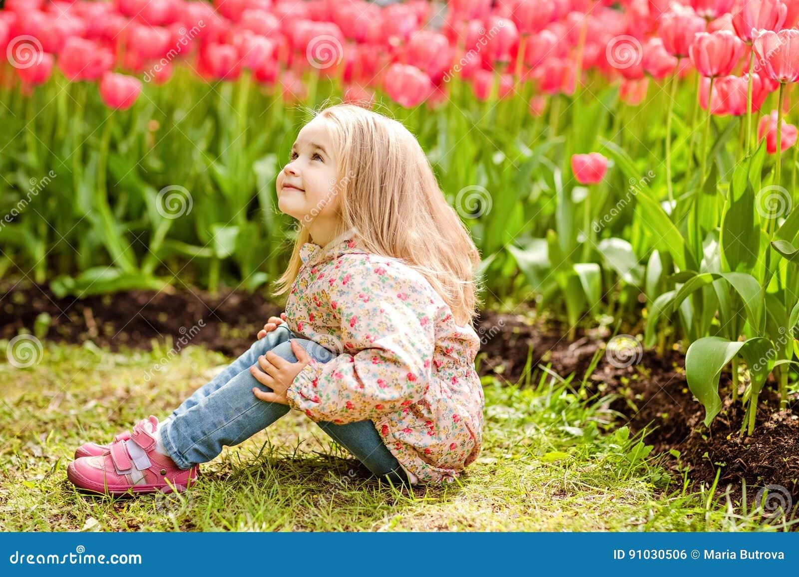 Belle fille blonde très douce dans un manteau rose se reposant près du