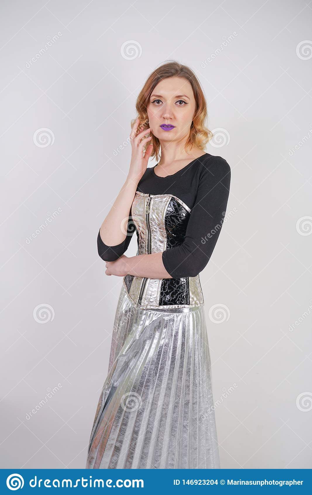 Belle fille caucasienne utilisant le corset futuriste de PVC et la jupe m?tallique de plaid avec les chaussures de course refl?t?