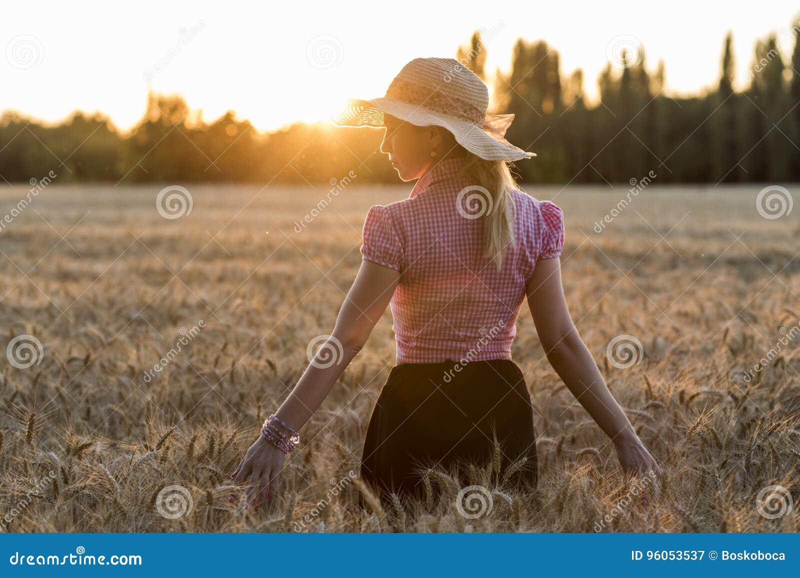 Belle fille dans la marche par le champ de blé