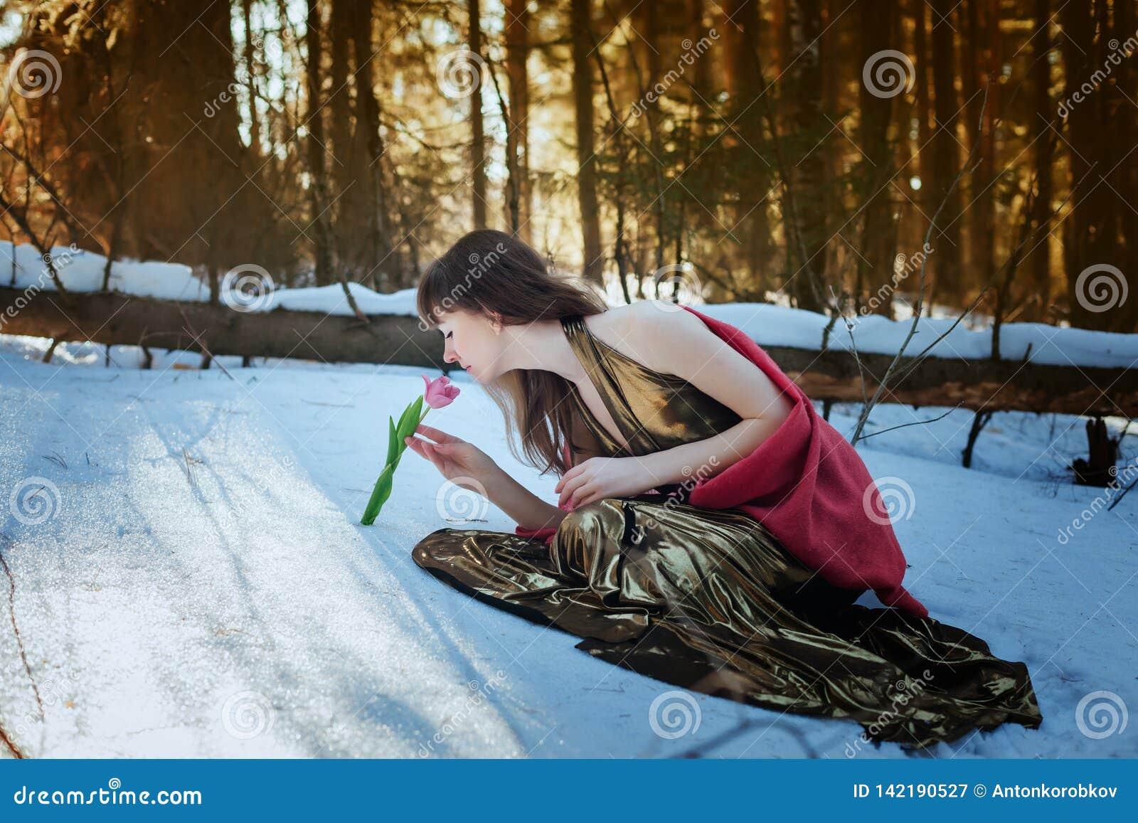 Belle fille dans la robe d or se reposant dans les bois du soleil de neige au printemps et la tulipe de contacts