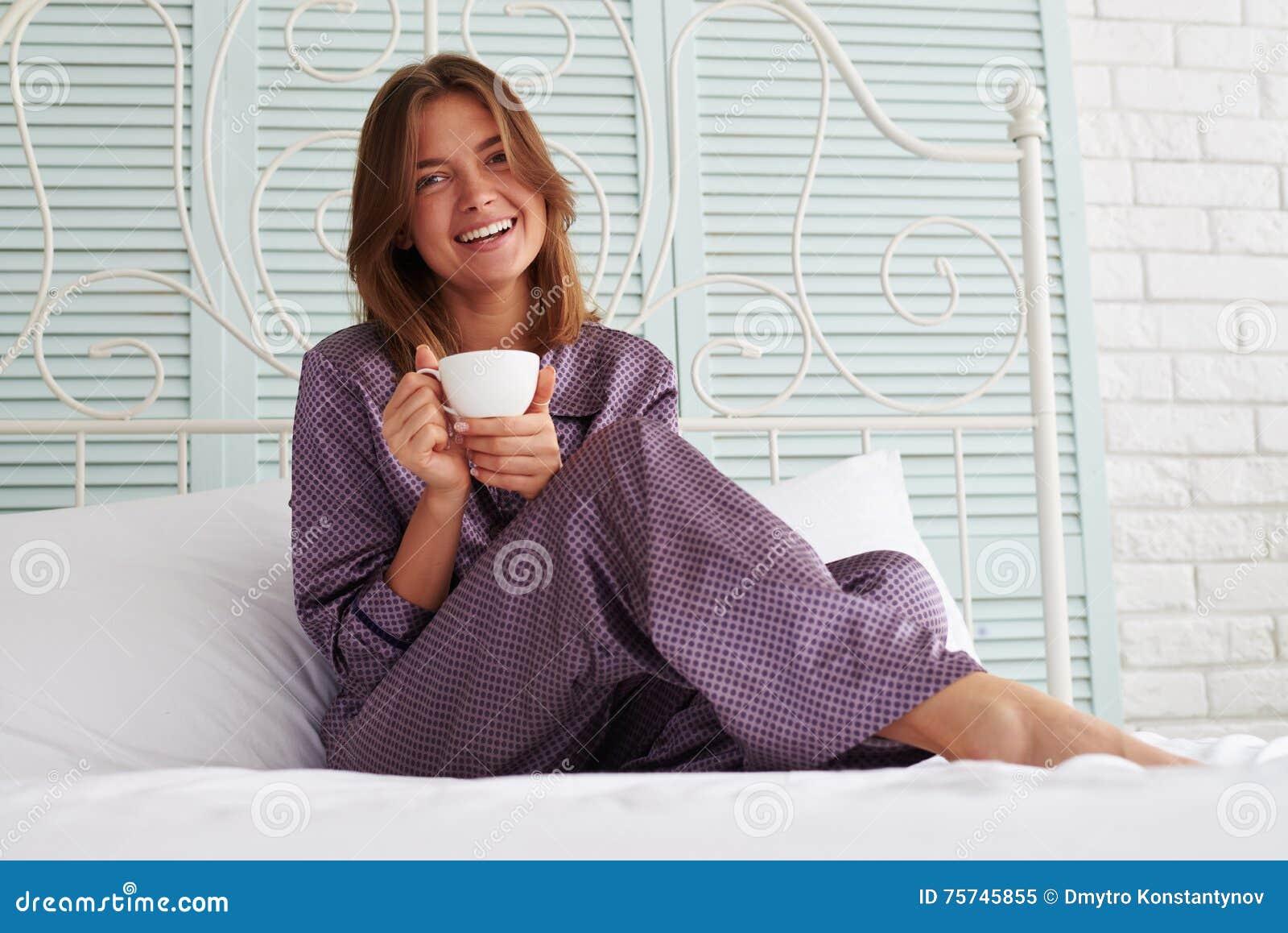 Belle fille dans le nuit-costume se reposant au chevet avec une tasse o