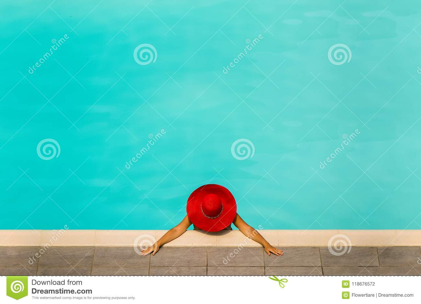 Belle fille dans un maillot de bain et un chapeau rouge dans une piscine d eau bleue
