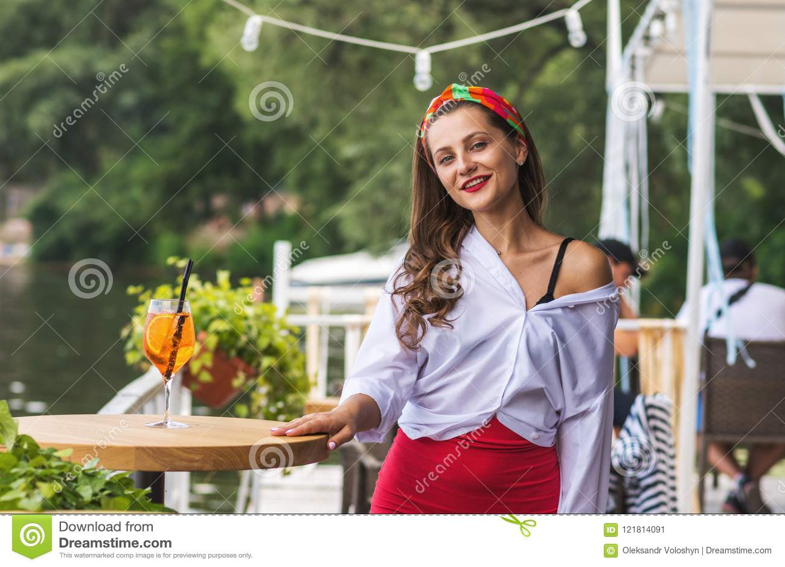 Belle fille dans une barre et avoir de plage un cocktail