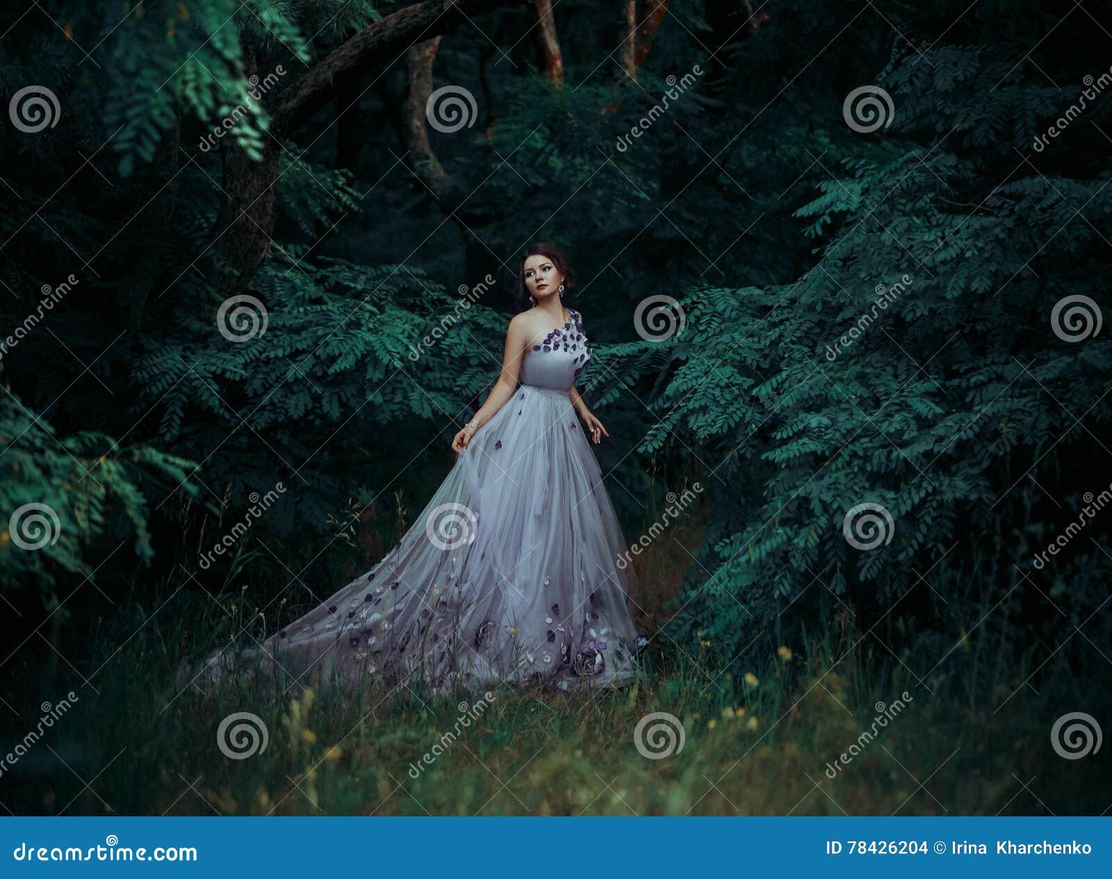Belle fille dans une longue robe magnifique, promenade parmi les arbres