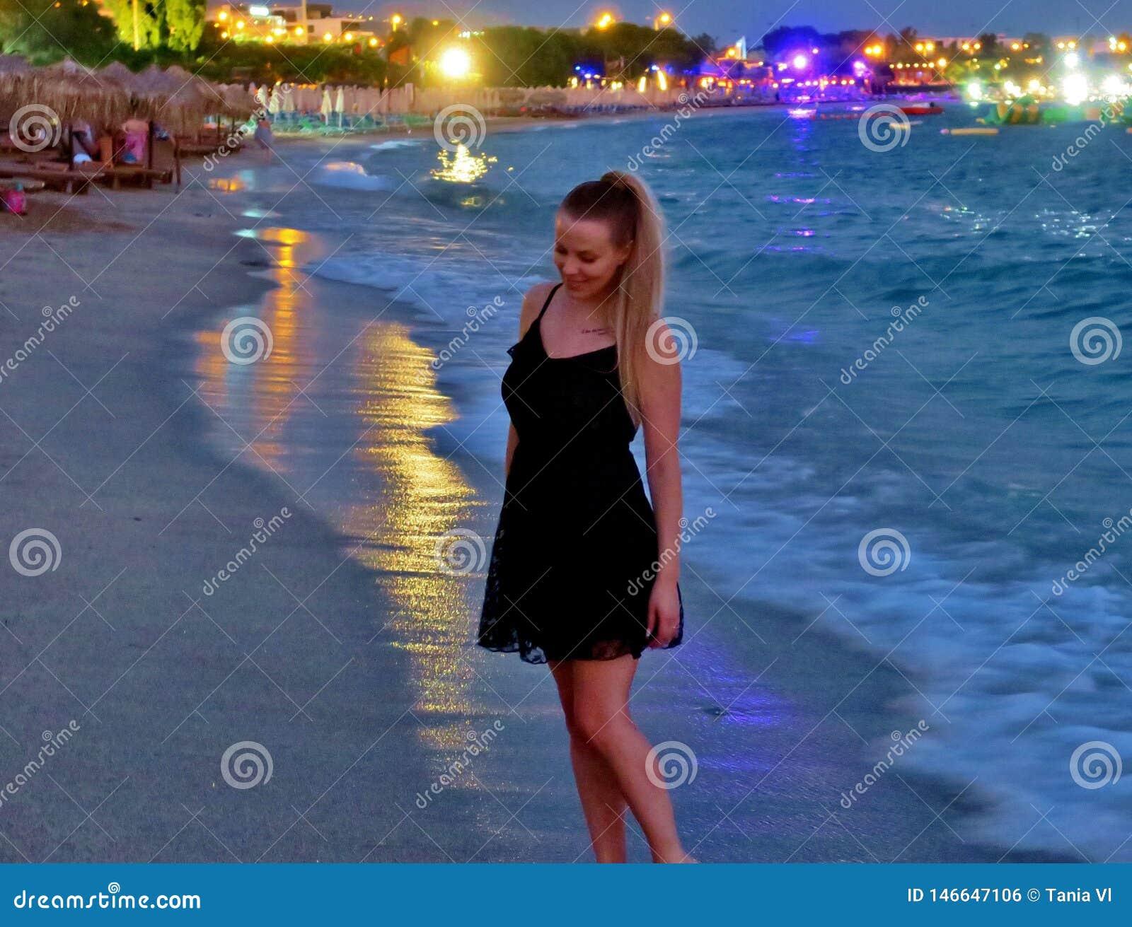 Belle fille dans une robe noire par la mer