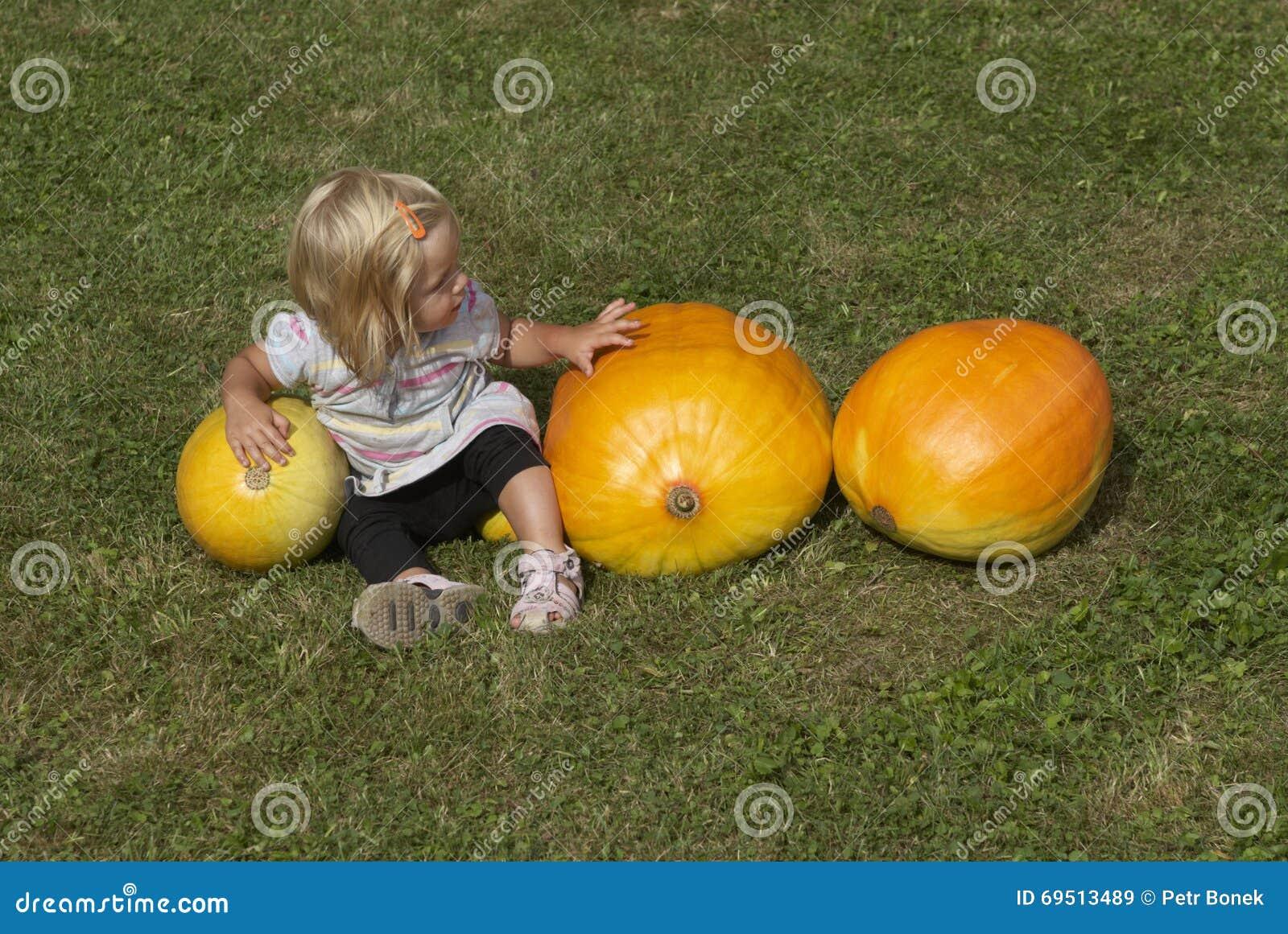 Belle fille de petit enfant ayant l amusement avec l agriculture sur la correction organique de potiron