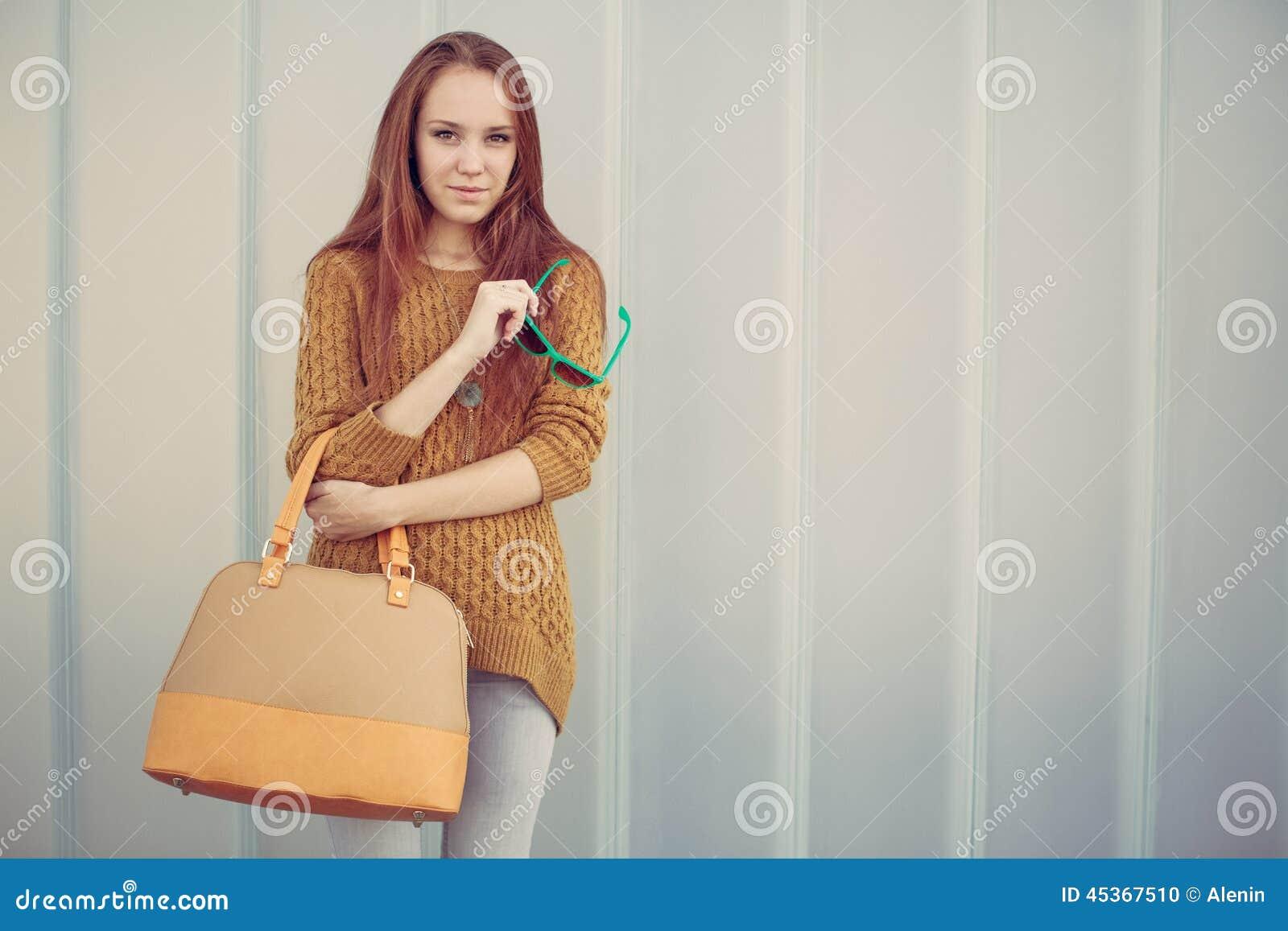 Belle fille de roux avec le grand sac à la mode se tenant près du mur gris