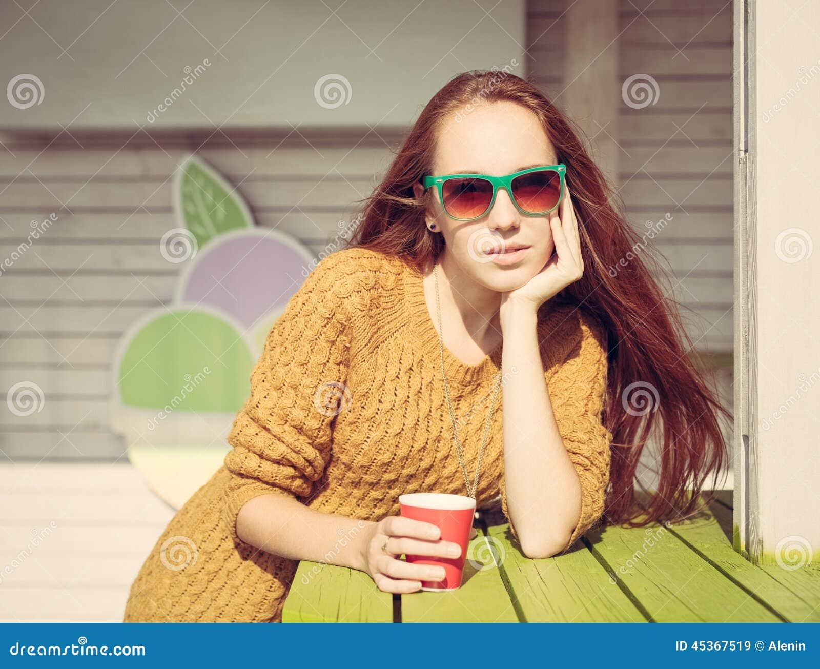 Belle fille de roux dans des lunettes de soleil pour la table extérieure de café d été