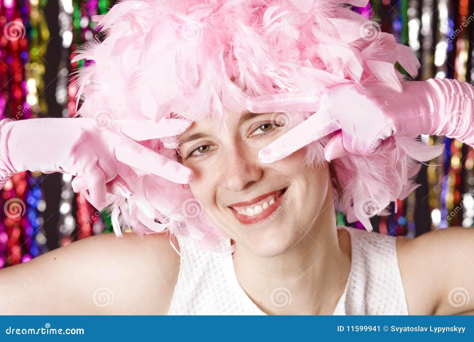Belle fille de sourire avec la perruque du plumage rose
