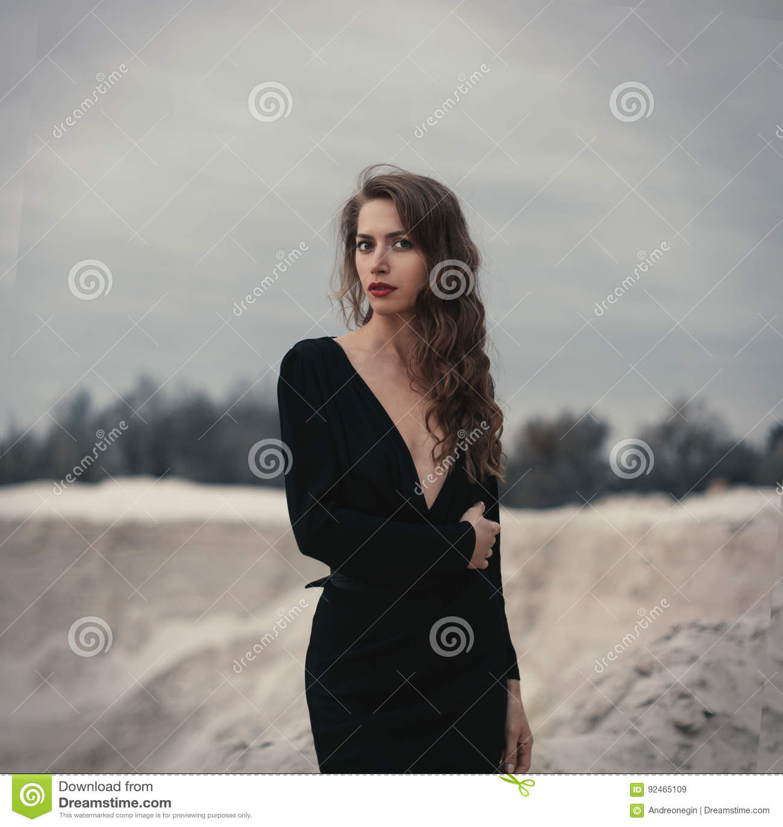 Belle fille dedans dans la robe noire de vintage avec les cheveux bouclés posant sur le sable Femme dans de rétros dres Émotion s