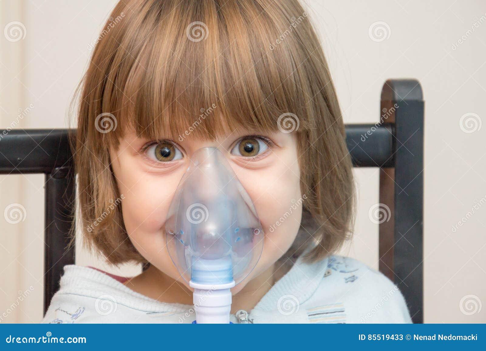 Belle fille employant le masque d inhalation