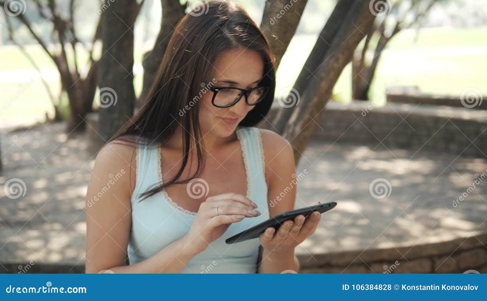 Belle fille gaie avec une tablette se reposant en parc sur un banc sur Sunny Day, concept en ligne d achats