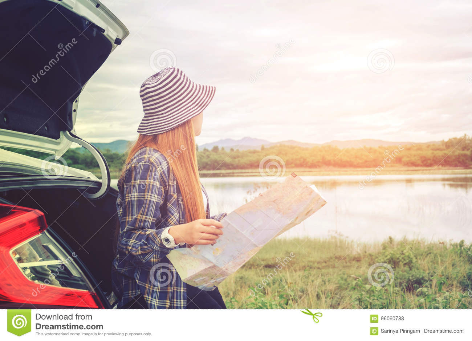 Belle fille heureuse voyageant dans une voiture de berline avec hayon arrière avec la carte