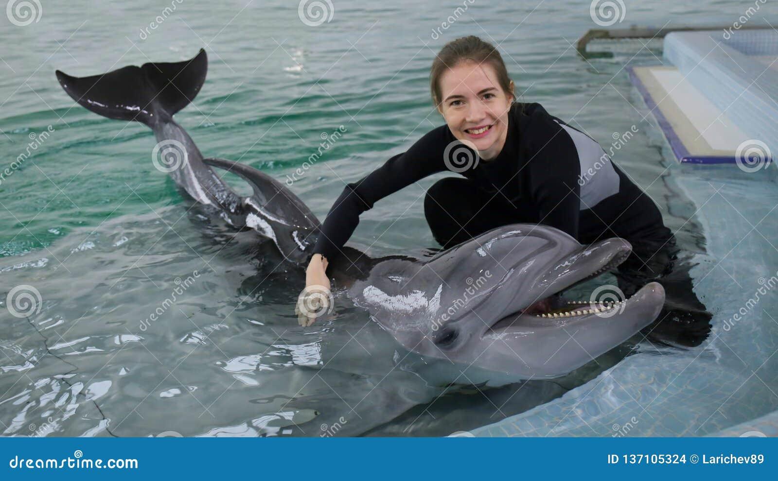 Belle fille jouant dans la piscine avec un dauphin
