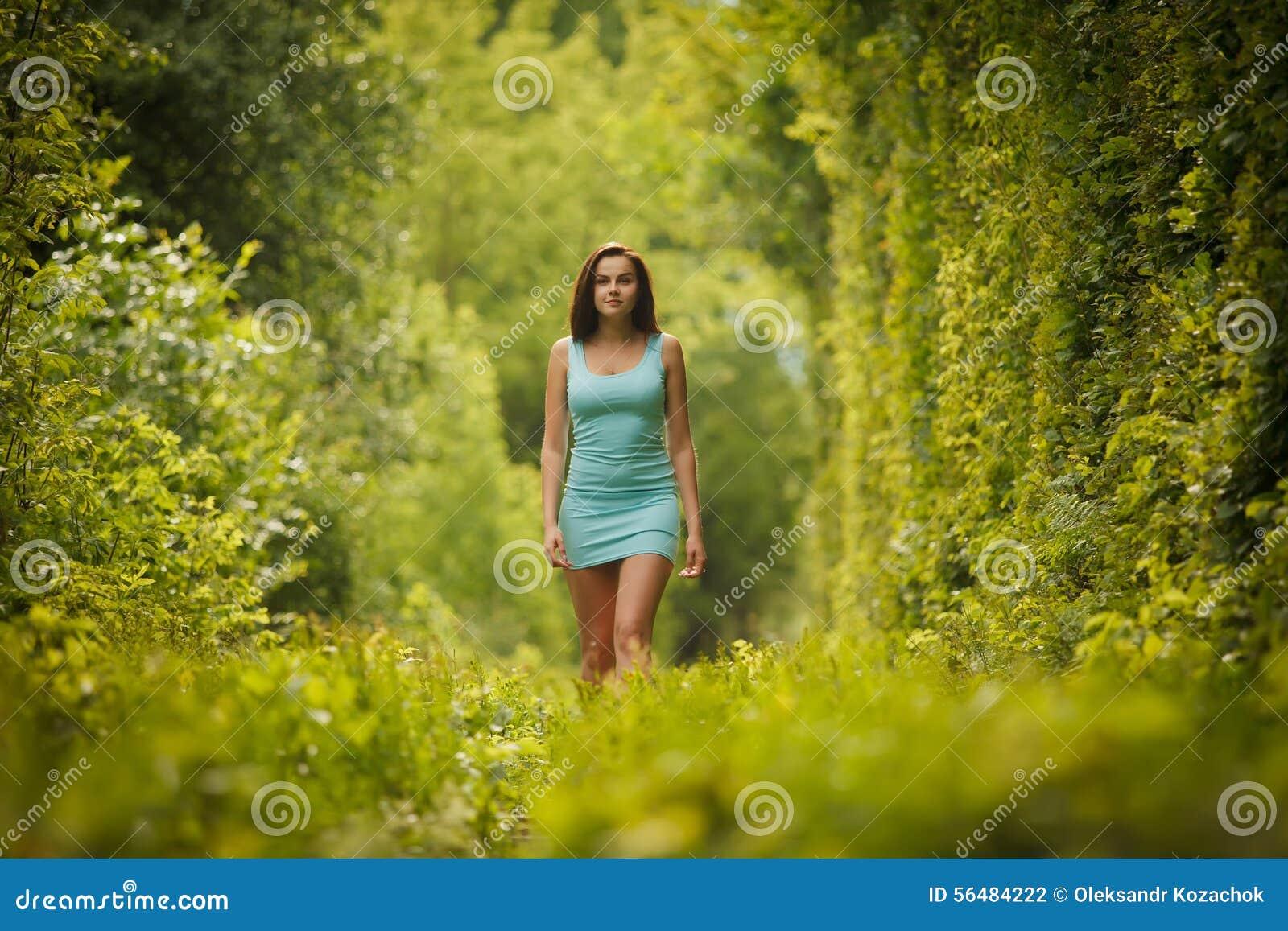 Belle fille marchant par le tunnel de nature