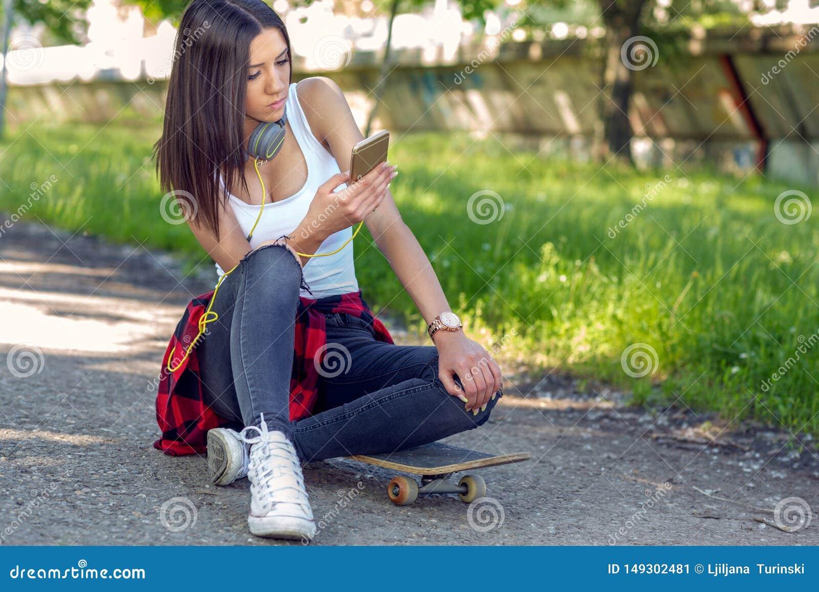 Belle fille s asseyant ? la planche ? roulettes et au t?l?phone portable d utilisation Dehors, mode de vie urbain