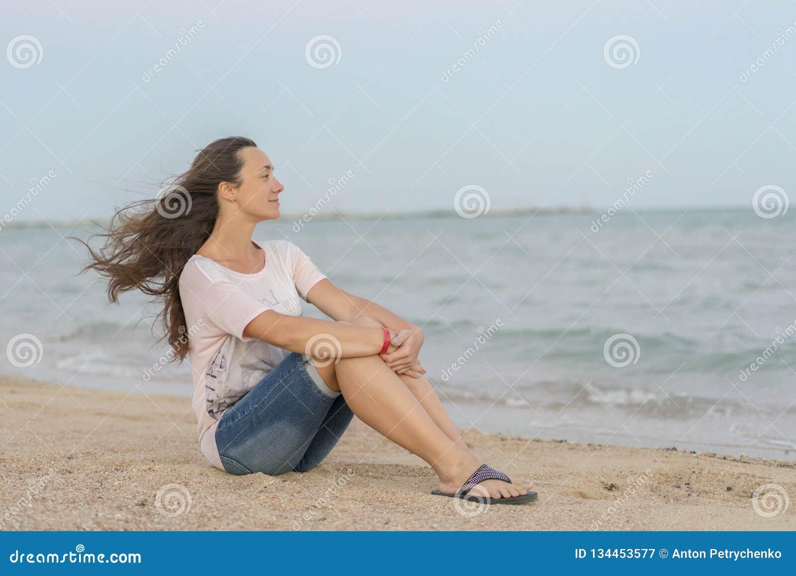 Belle fille s asseyant sur la plage Le milieu a vieilli la femme se reposant à la plage près de la mer jeune, belle femme avec le